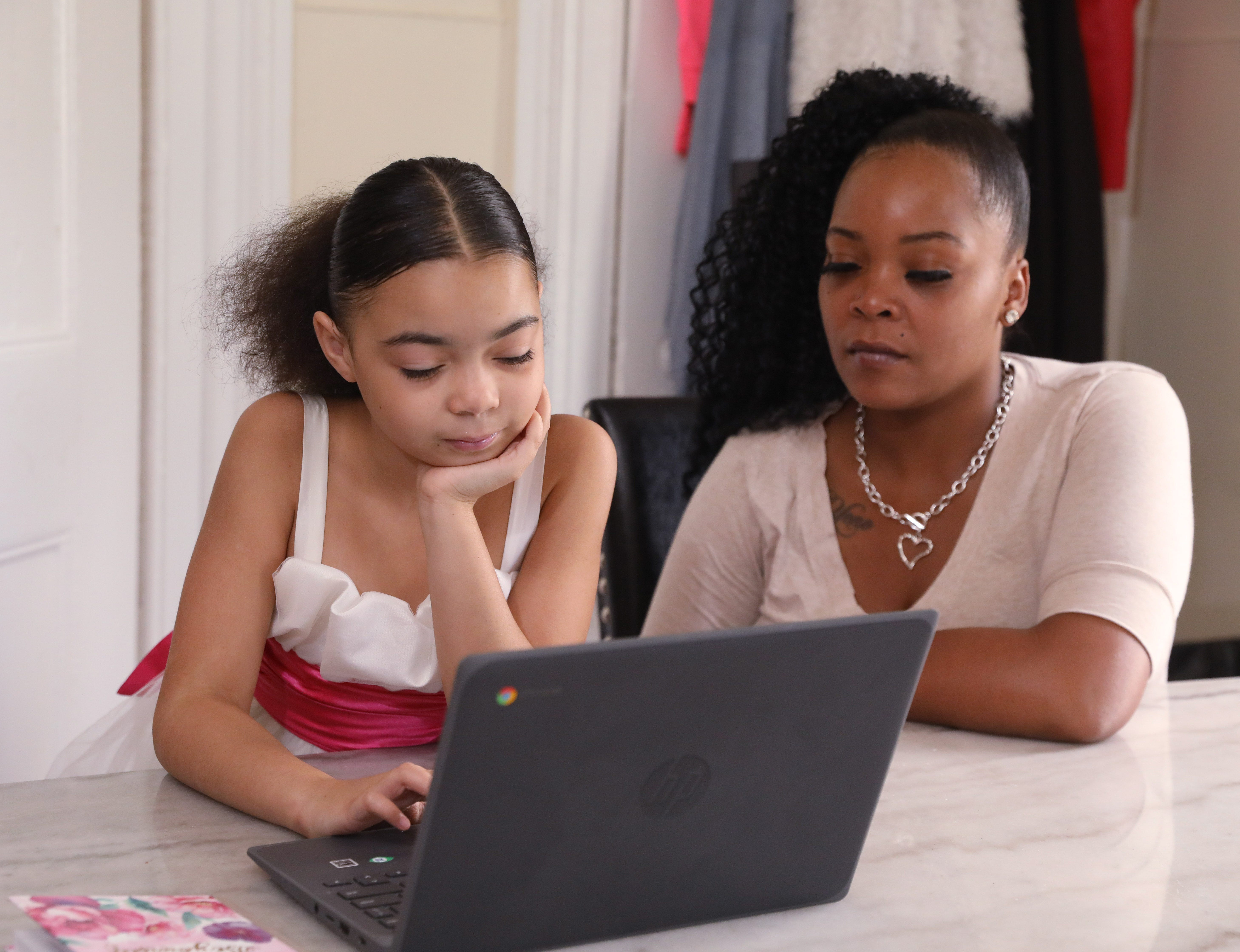 Kendra Smith helps her daughter Diamond Yeno submit her math homework at their home in Poughkeepsie on Sept. 24, 2020.