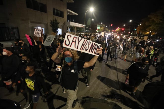 """During a Rochester Black Lives Matters march, a protester holds a """"Say His Name' sign in reference to Daniel Prude, who died in police custody in March."""