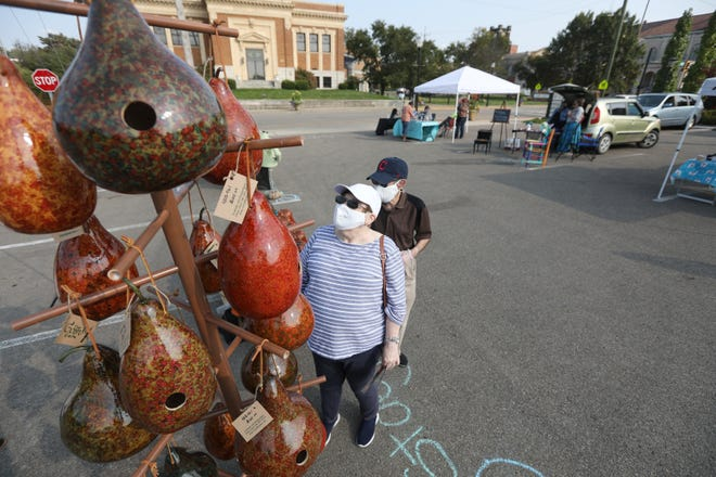 VIcki Santos and her husband Bob look at gourd birdhouses by Stoey Stout during the ArtCoz art market on Friday. The market was the artists' first public activity since the start of the COVID-19 pandemic.