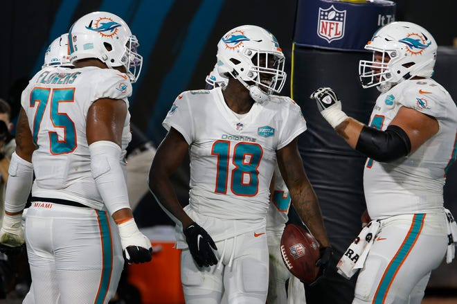 Dolphins receiver Preston Williams celebrates his TD catch against Jacksonville with Ted Karras (right) and Ereck Flowers (75).