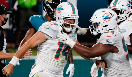 Ryan Fitzpatrick celebrates with defensive tackle Christian Wilkins after scoring a touchdown against the Jacksonville Jaguars.