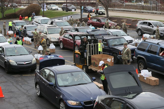 Members of the 145th National Guard unit of Stow help distribute food at Akron-Canton Regional Foodbank on March 26.