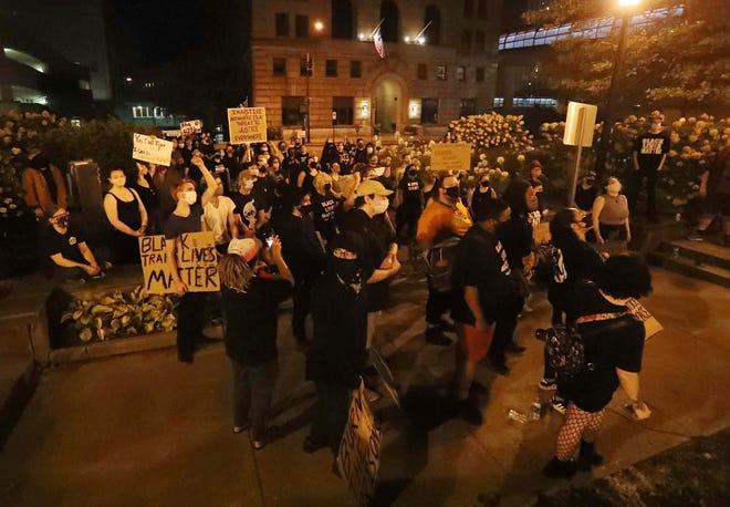 Demonstrators listen to speakers in front of the Summit County Courthouse and across the street from City Hall in Akron after a march from Highland Square to protest no charges being brought against the Louisville, Ky., police officers who were involved in the killing of Breonna Taylor.
