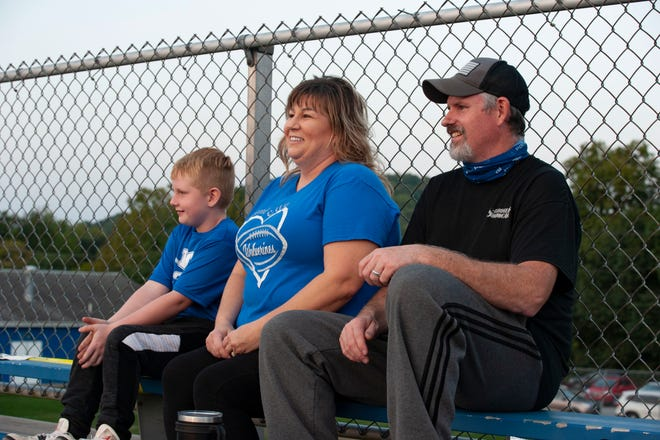 Parents Michelle Bales, center, and husband Richard Bales, right, and 7-year-old son Ryan Bales, sit at the Ellwood City homecoming football game Friday and watch their son Andy Vrabel, a senior at Ellwood.