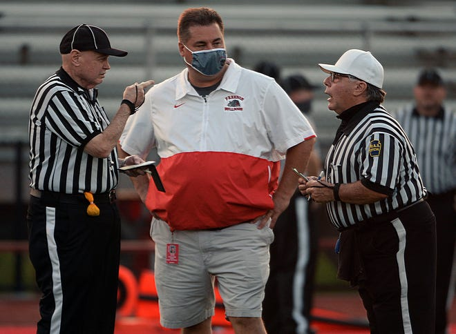 Former Freedom Area High School head football coach, now Freedom AD, John Rosa listens to referees talk before the Bulldogs game against Neshannock in 2020.