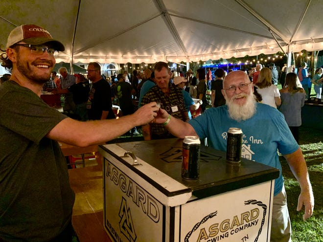 Ray Turner, right, serves up brews from Columbia's local Asgard Brewing Co. & Taproom, who were the main organizers for Friday's Oktoberfest event.  Oktoberfest featured nearly a dozen regional breweries and raised more than $40,000 for Columbia's local Room in The Inn shelter. (Staff photo by Jay Powell)