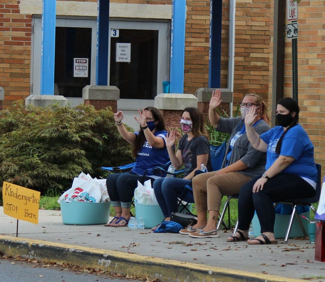 Kindergarten teachers line up along the front of East Dover Elementary greeting students as they drive by for the start of the school year. Classes are online now, but the school board will vote on a partially in-person plan Oct. 20.