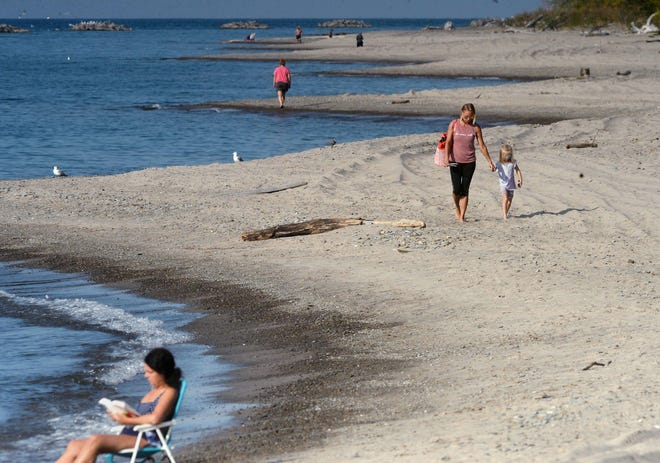 Millcreek Township resident Danielle Santini walks with her 5-year-old daughter Carter Santini near Barracks Beach at Presque Isle State Park on Sept. 25.
