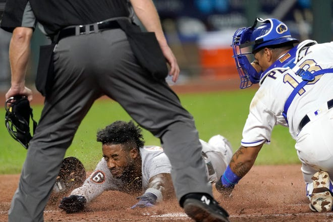 Detroit Tigers' Niko Goodrum beats the tag by Kansas City Royals catcher Salvador Perez to score on a sacrifice fly by Eric Haase during the seventh inning of Friday's game at Kauffman Stadium. Despite the run, the Royals held on for a 3-2 win.