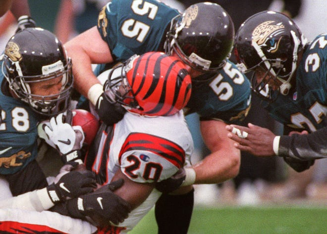 From left, Jaguars safety Dana Hall, linebacker Tom McManus and safety Chris Hudson combine to tackle Bengals running back Garrison Hearst on Dec. 1, 1996.