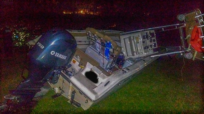 The power boat, its center console section damaged from the impact, settles in the backyard of a home along the Ortega River Friday night after the top hit the closed Ortega Bridge, according to Jacksonville Fire and Rescue.