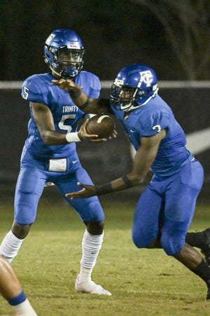 Trinity Christian quarterback Ja' Cory Jordan hands off the ball to running back Treyaun Webb in second a September game. Trinity Christian plays Ocala Trinity Catholic with a shot a the state title on the line Friday in Ocala.