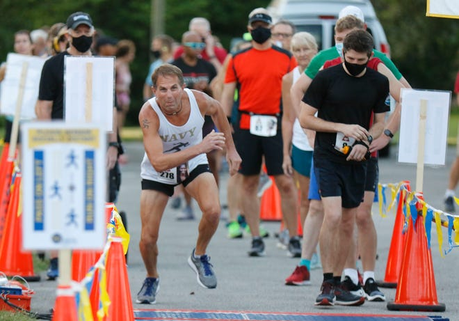 Mark Tulowiecki jumps off the line as Cody Anderesen-Otten sets his stopwatch in a staggered start for the Leading Edge 5K on Lake Hollingworth in Lakeland.