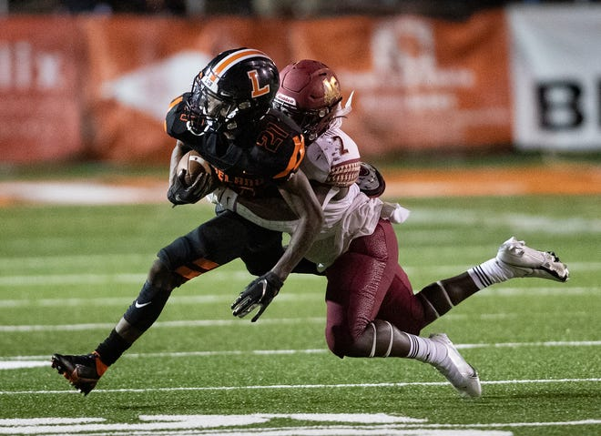 Lakeland's Reggie Kellum (21) is tackled by Lake Gibson's Kaleb Ross (2) at Bryant Stadium in Lakeland on Friday.