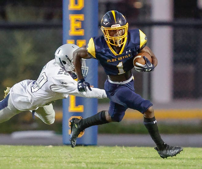 Winter Haven's Jakobe Lane avoids a tackle from Ridge's Ty Footman as he breaks into the open on Friday night at Denison Stadium in Winter Haven.