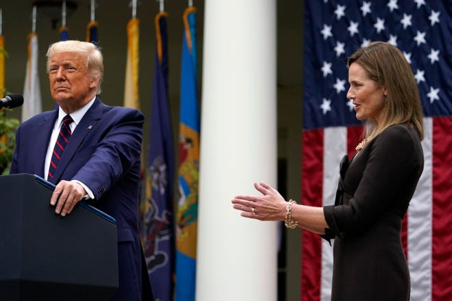 Judge Amy Coney Barrett applauds as President Donald Trump announces Barrett as his nominee to the Supreme Court, in the Rose Garden at the White House on Saturday in Washington.