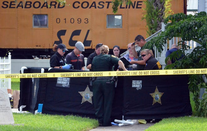Polk County sheriff's deputies and crime scene investigators hover around a body discovered in front of the Mulberry Phosphate Museum on Friday morning just off Hwy. 37 in Mulberry. BILL KEMP/THE LEDGER