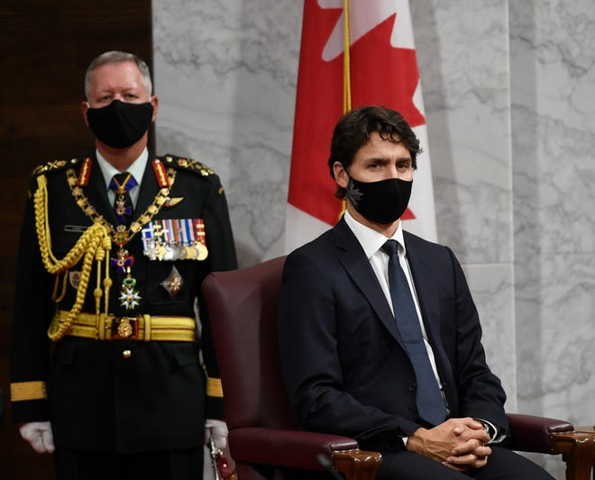 Chief of Defence Staff Jonathan Vance, left, and Canadian Prime Minister Justin Trudeau listen to Gov. Gen. Julie Payette deliver the throne speech in the Senate chamber  on Wednesday in Ontario.