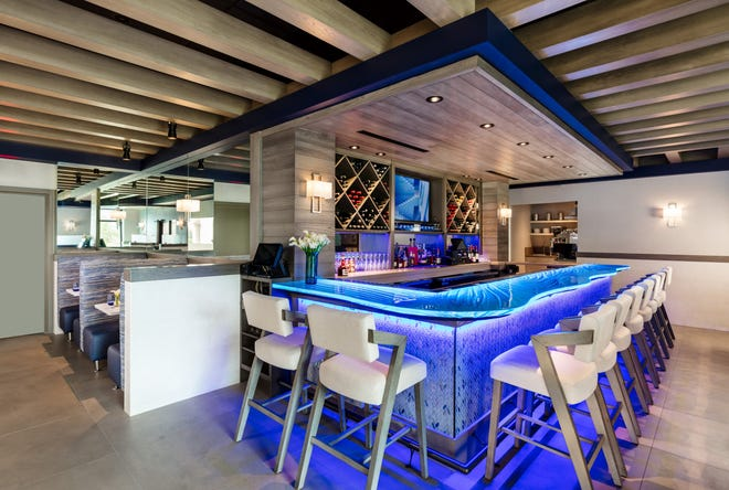 The custom-made three-layer glass bar at Acqua Cafe lights up and glows a Caribbean blue hue. The bottom layer resembles a tide-swept ocean floor. [Photo by Kim Sargent/courtesy Acqua Cafe]