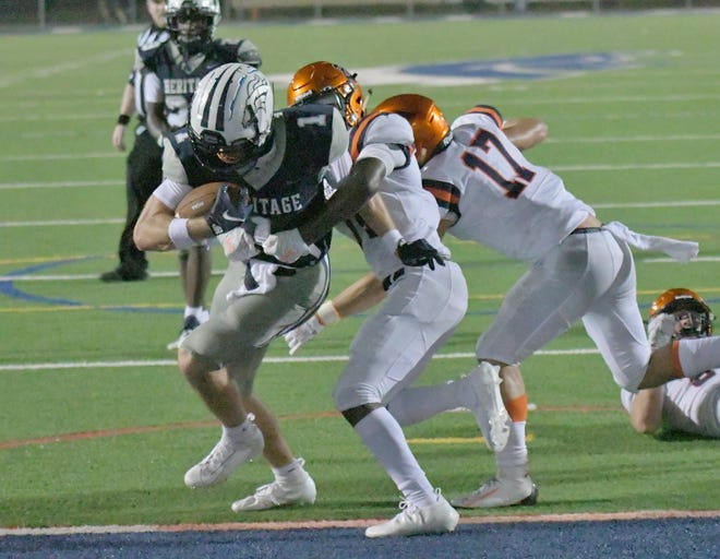 American Heritage wide receiver Brandon Schabert scores the game's first touchdown on a rushing play in the second quarter. In its first game since the death of coach Brian Sheridan, Heritage beat Benjamin 24-3.