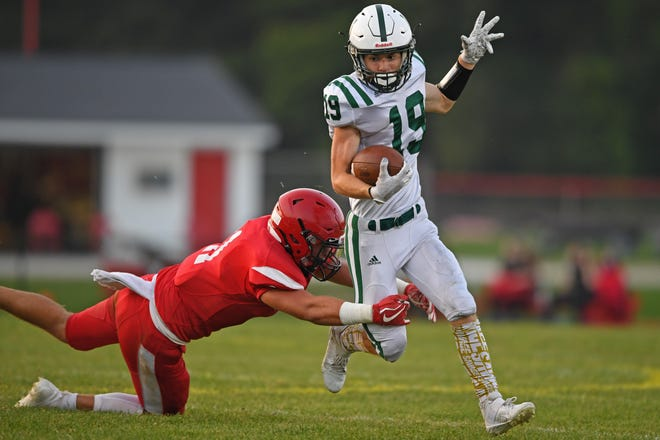 Cloverleaf's Michael Williams runs the ball while being grabbed by Field's Caden Contant during the first half of Friday's game at Field High School.