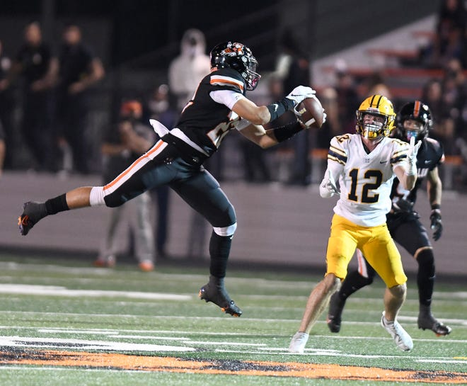 Massillon's Jaidan Wise picks off a pass intended for St. Ignatius ' Alec LaSpina in the first half.