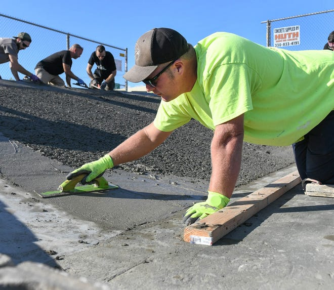 Adam Farley, a volunteer for the Canton Skateboard Association, finishes concrete on a bank ramp being installed at the skateboard park in West Park.
