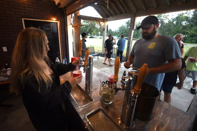 A guest at Ironclad Golf gets his cup filled with beer Friday night during a food truck and driving range event at the course.