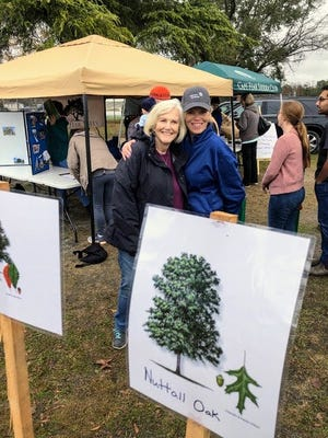 "Connie Parker, chair of the Alliance for Cape Fear Trees, gets a ""human hug"" from a ""tree hugger"" during a tree planting on Dec. 14, 2019. [COURTESY OF THE ALLIANCE FOR CAPE FEAR TREES]"
