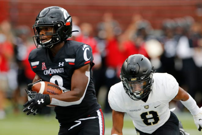 Army's Javhari Bourdeau chases Cincinnati wide receiver Michael Young, left, during a touchdown catch in a 24-10 loss to the No. 14 Bearcats. JAY LAPRETE/AP
