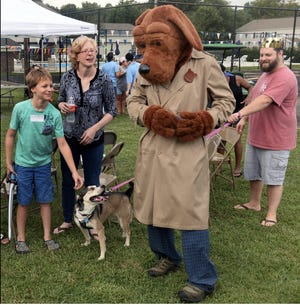 McGruff the Crime Dog is greeted by Andrew and Chris West, their son Nathan West and the family pet Sweetie Pie during National Night Out 2019.