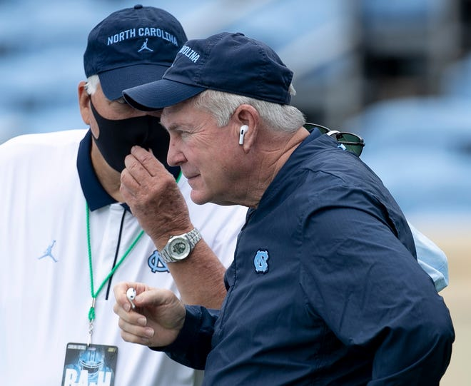 Coach Mack Brown, front, confers with North Carolina staff member Ken Browning before the Tar Heels' victory against Syracuse to open the season.