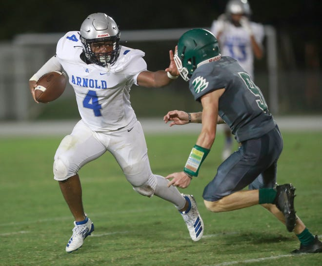 Arnold's Josiah McCall (4) runs the ball past South Walton's Logan Stewart (9). Arnold faced off with South Walton for a football game on Sept. 25, 2020.