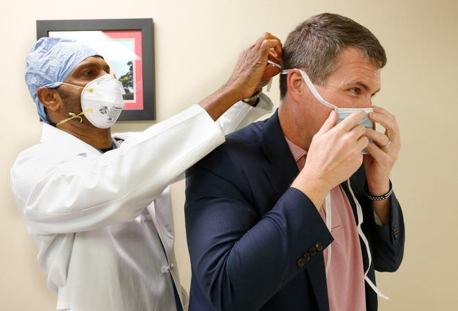 The Crimson Care Primary & Urgent Care clinics of Dr. Ramesh Peramsetty, seen here in a file photo helping Mayor Walt Maddox into a surgical mask, are now offering the Moderna vaccine for COVID-19. [Staff file photo/Gary Cosby Jr.]