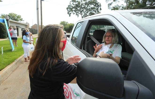 United Way volunteers and staff give away masks in front of the office on 6th Street in Tuscaloosa, August 13, 2020, during a drive-thru mask distribution. Annette Smallwood gives packages of masks to Anne Odom. [Staff Photo/Gary Cosby Jr.]