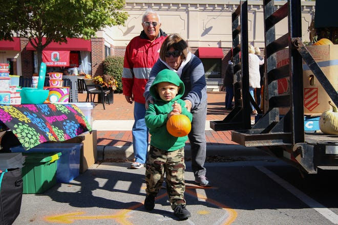Logan Masters, 2, of Grove City runs with a pumpkin as his grandmother, Elona Miller, and grandfather, Jack Miller, chase after him at the Harvest Market Oct. 12, 2019, in Grove City. This year's market began Sept. 26 and continues Saturday, Oct. 3, as well as Oct. 10 and 17.