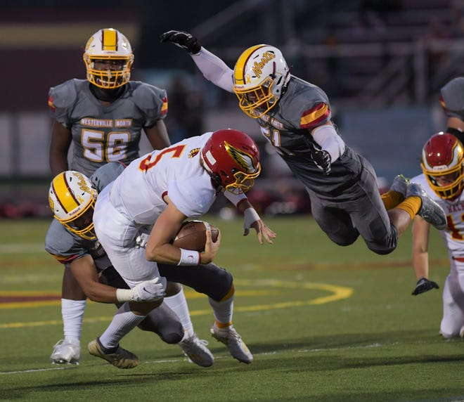 Westerville North's Mitchell Gillam leaps to help stop Big Walnut quarterback Jagger Barnett during the teams' game Sept. 25. The Warriors open the playoffs Oct. 9 at home against New Albany.