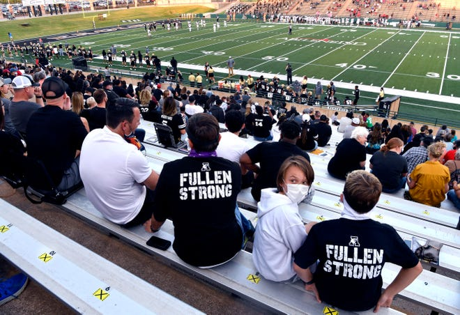 Cade Reese, 11, looks over his shoulder as he sits between Justin Reese and his friend Cash Churchill, also 11. The three were watching the Abilene High Eagles play Amarillo Tascosa Friday at Shotwell Stadium. Many in the crowd wore shirts supporting Eagles Coach Mike Fullen who is recovering from cancer surgery and was not at the game.