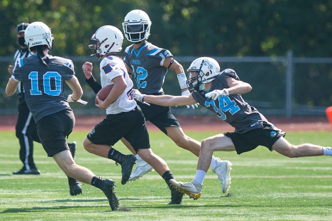 BFA-Fairfax/Lamoille's Shaun Gibson, center, tries to escape a trio of tacklers after making a catch during a 7-on-7 high school football game at Buck Hard Field on Saturday, Sept. 26, 2020.