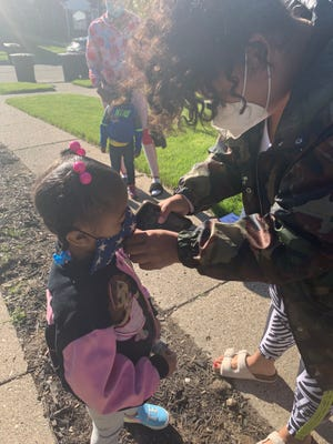 A child gets help putting on a mask to prepare for a day at Crystal Swann Learning Center, a child care center in Detroit, in June 2020.