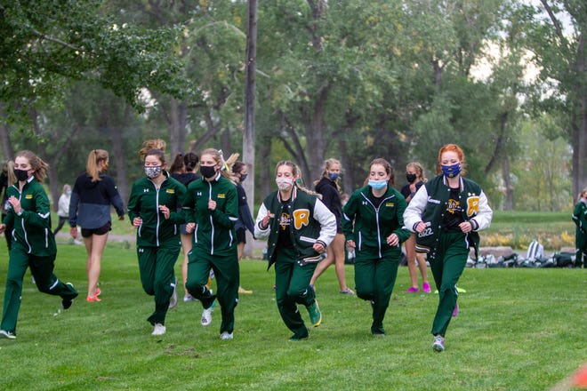Members of the CMR Rustlers cross country team warm-up in face masks due to the ongoing COVID-19 pandemic at the Great Falls at the Anaconda Hills golf course Sept. 25. Cascade County officials say some businesses are not complying with rules requiring that patrons and employees wear masks. Capacity limits inside buildings also are being ignored in some cases.