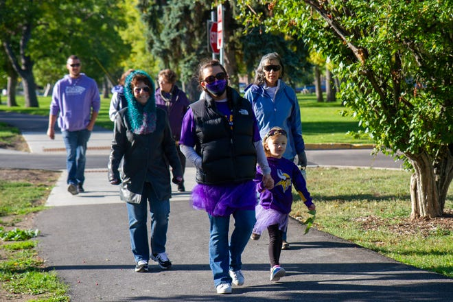 Amy Remmel (center) walks with her mother Nancy Loncki (left) and other friends and family at Gibson Park for the Cascade County Walk to End Alzheimer's, which was held virtually on Saturday, Sept. 26, 2020. Remmel organized the group in secret to surprise Loncki and show her how many people support her. Loncki's husband was diagnosed with Alzherimer's about two-and-a-half years ago.