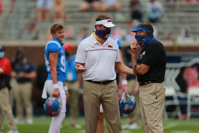 First-year Ole Miss coach Lane Kiffin, left, and Florida coach Dan Mullen chat at midfield last Saturday before their game in Oxford.