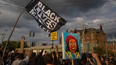 Flags and signs wave through the air at sunset as protesters march through into the Nulu neighborhood on Friday evening. Sept. 25, 2020