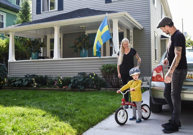 Sara and Ethan Durner, with their 3-year-old son Casper, in the driveway of their Lansing home on Sept. 26, 2020.  Two years ago, they learned their son had a small amount of lead in his system. They participated in Lansing's lead-abatement program this summer. Their home is now safe from lead.