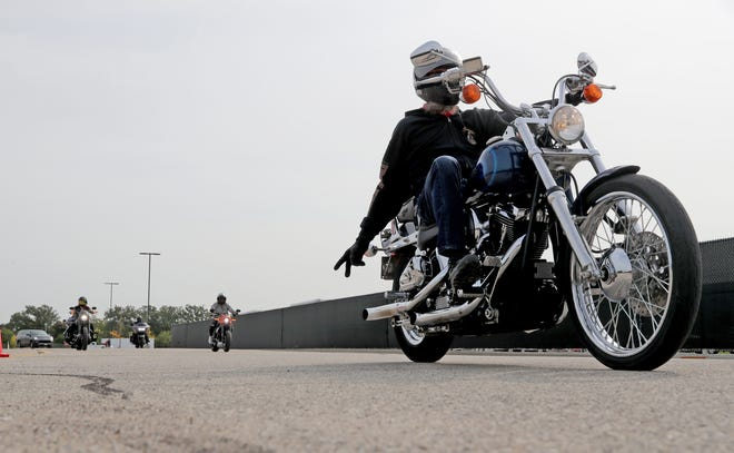 A motorcyclists gives the peace sign while heading out for the 2020 Multicultural Unity Ride that started at the Harley-Davidson Product and Development Center on West Capitol Drive in Wauwatosa on Saturday.