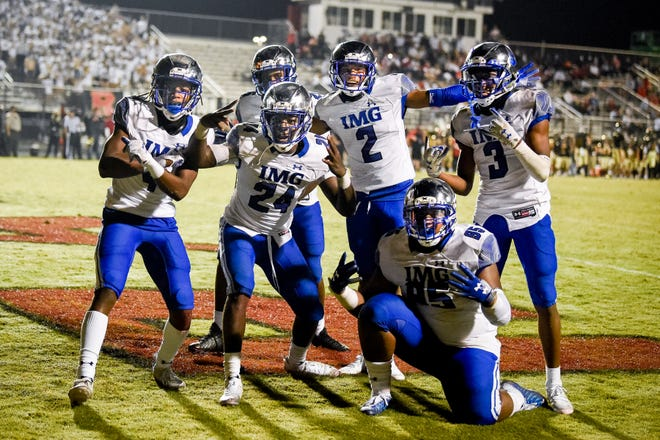 IMG Academy's Kamari Wilson (24) celebrates his interception against Ravenwood with teammates during the second half at Ravenwood High School in Brentwood, Tenn., Friday, Sept. 25, 2020.