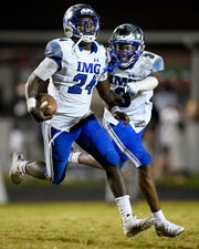 IMG Academy's Kamari Wilson (24) celebrates his interception against Ravenwood with IMG Academy's Oj Burroughs (3) tduring the second half at Ravenwood High School in Brentwood, Tenn., Friday, Sept. 25, 2020.
