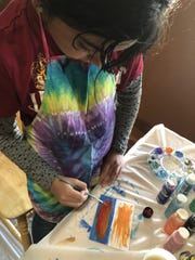 Anelise Elmquist paints a card for her business, Art for the World.