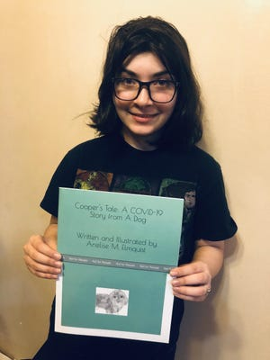 "Anelise Elmquist poses with the book she wrote, ""Cooper's Tale: A COVID-19 Story from a Dog."""